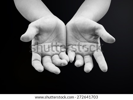 Black and white two female open empty hands with palms up on dark background: Pray for support and help gesture : Helping hands needed concept: International Migrants Day