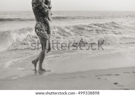 Black and white unfocused silhouette of mother carrying little child walking along sand beach sunset background. Back side view