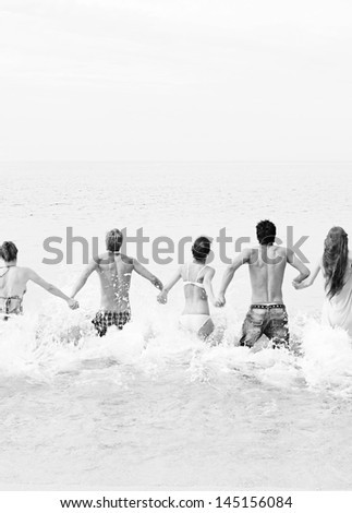 Black and white view of a group of five mixed friends holding hands and running into the sea water together, being spontaneous and having fun while on a summer vacation on a beach. - stock photo