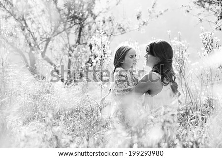 Black and white view of a mother and daughter relaxing together, hugging and joyfully smiling in a field of sunshine and spring flowers on a summer holiday. Family activities and outdoors lifestyle. - stock photo