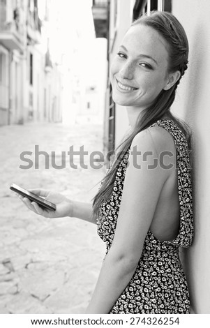 Black and white view of a young woman visiting a picturesque stone pavement street, using a smartphone mobile to get directions, smiling in a destination city on holiday, outdoors. Travel technology. - stock photo