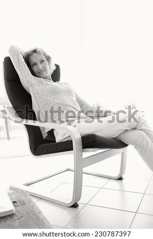 Black and white view of an attractive mature woman sitting on a comfortable armchair against light windows at home, lounging during a bright sunny day, indoors. Home living well being lifestyle.