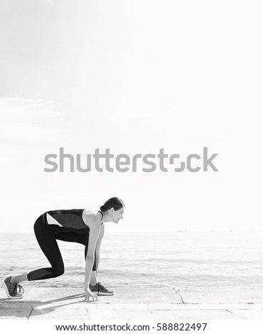 Black and white view of athlete woman preparing to run against sky and sea space, healthy lifestyle. Wellness and well being, training sport, active female care and fitness. Graphic body shape figure.