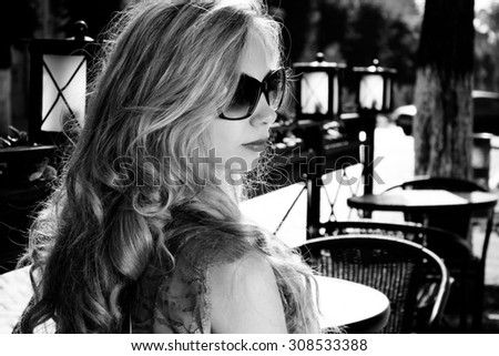 Black and white view of beautiful blonde sexy woman in red dress beauty jewelry model slim girl with makeup hairstyle smiling and looking happy posing - stock photo