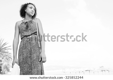 Black and white view of elegant beautiful african american black teenager girl standing against sky on holiday, looking away, on beach outdoors. Young bohemian woman aspirational lifestyle, exterior. - stock photo