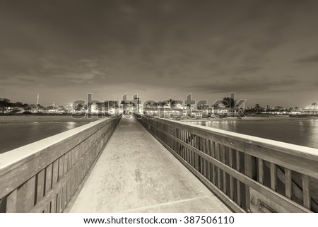 Black and white view of pier at dusk.