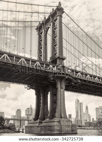 Black and white view of the Manhattan bridge in New York with the city skyline on the background - stock photo