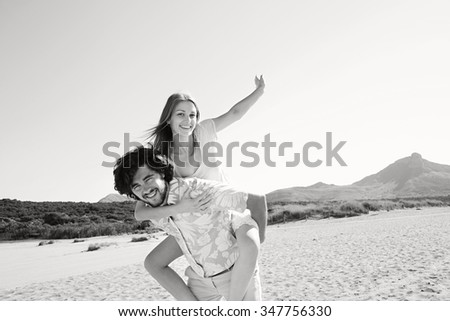 Black and white view of young tourist couple on holiday, with man carrying girl in piggyback on beach destination, outdoors space. Romance and dynamic honeymoon fun lifestyle, summer exterior. - stock photo