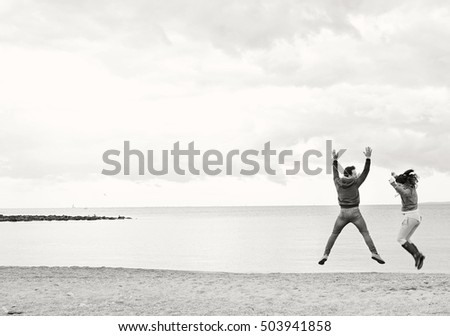 Black and white view of young tourist man and woman jumping up together in beach on a winter holiday with moody skies, outdoors fun. Travel and dynamic lifestyle couple, cold seasonal exterior.