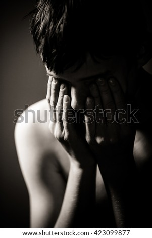 Black and White Waist Up of Young Shirtless Teenage Boy Holding Face in Hands in Studio with Dramatic Lighting and Dark Background - Upset Boy Crying or Upset and Hiding Face in Hands