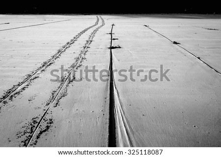 black and white wheel track and rope on beach