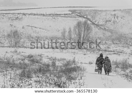 Black and white winter landscape with snow and two going down the road people