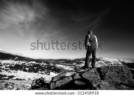 black and white winter mountain landscape with hiker on the top of the high rock  - stock photo