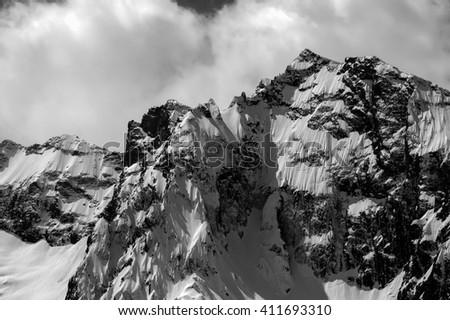 Black and white winter mountains in cloud. Dombay. Caucasus Mountains, region Dombay. View from ski slope. - stock photo