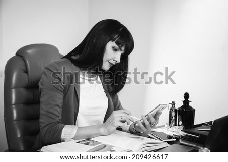 Black and white.Woman in a business suit. Business woman sitting at the table, working with the computer. Business, work, business woman - business concept girl. The idea about the woman's business.