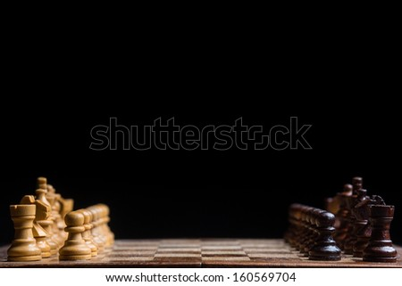 Black and white wooden chess pieces on board with black background - stock photo