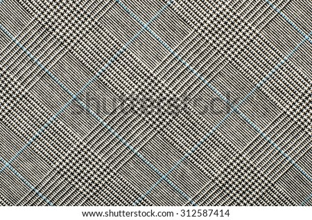 Black and white wool twill pattern. Black and white with blue houndstooth pattern in squares. Woven dogstooth check design as background. - stock photo