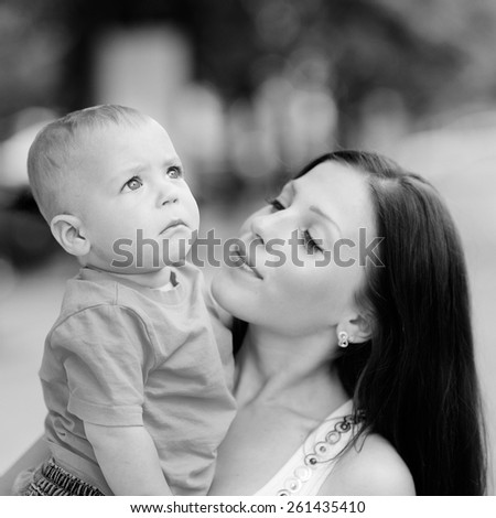 Black and white, 1 year baby in the arms of mother, blond, gray eyes, jeans, Mum young beautiful brunette with straight hair, a white T-shirt. Young mother with her baby in her arms. - stock photo