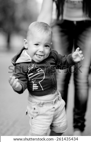 Black and white, 1 year baby with bagel, blonde, in a jacket with a hood,  jeans. Against the background of  trees. - stock photo