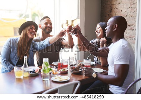 Black and white young adult couples celebrating with drinks after eating together at table in restaurant with large bright window in background