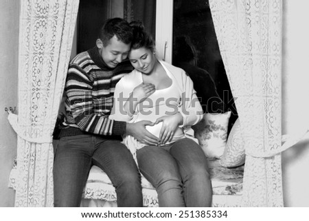 black and white, young couple sitting on the windowsill, his wife pregnant - stock photo
