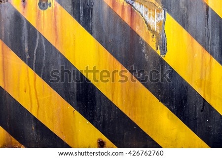 Black and yellow caution strips line painted on metal surface, rusty grunge background - stock photo