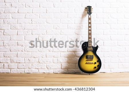 Black and yellow electric guitar in interior with wooden floor and white brick wall - stock photo