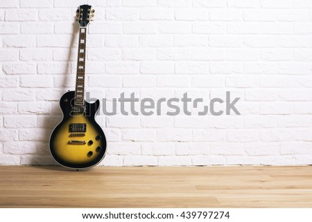 Black and yellow electric guitar in studio with wooden floor and white brick wall - stock photo