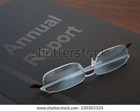 Black annual report folder and glasses on dark wood table close-up