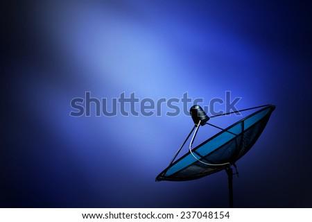 black antenna communication satellite dish on blue dark background - stock photo