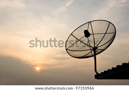 black antenna communication satellite dish over sunset sky
