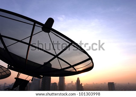 black antenna communication satellite dish over sunset sky in city - stock photo