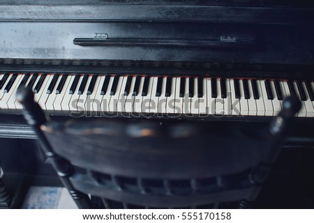 Black antique piano and a chair. General form