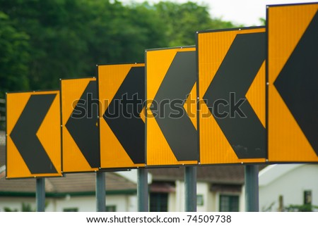 Black arrows on yellow traffic sign pointing left, Malaysia - stock photo