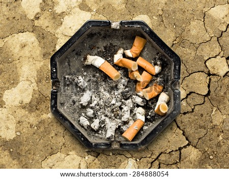 Black ashtray with cigarette stubs in closeup - stock photo