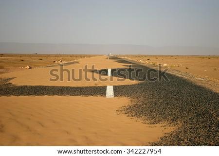 Black asphalt road full of sand through the desert - stock photo