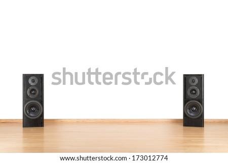 Black audio speakers on the floor. Wall isolated. - stock photo
