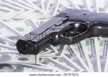 Black automatic pistol on background with one hundred dollar notes