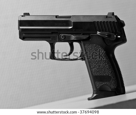 Black automatic pistol on gray