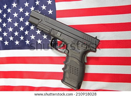 Black automatic pistol set against US flag - stock photo
