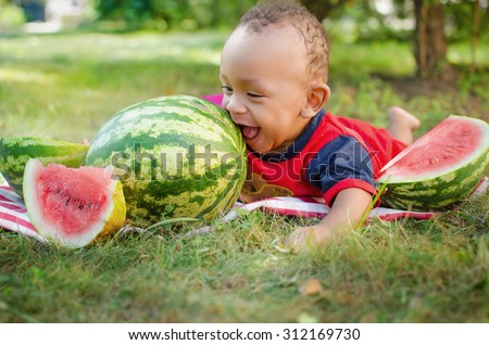 black baby boy lying on the grass and eating watermelon - stock photo