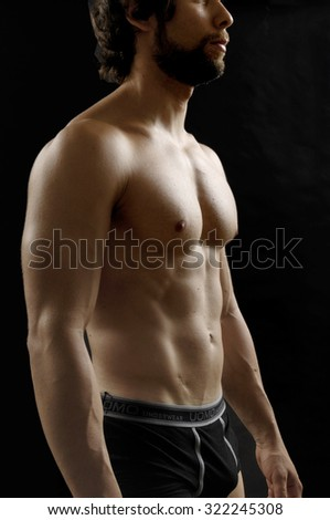 black background a naked man showing his body fitness, - stock photo