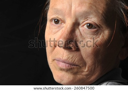 Black background portrait of a happy senior woman smiling at the camera
