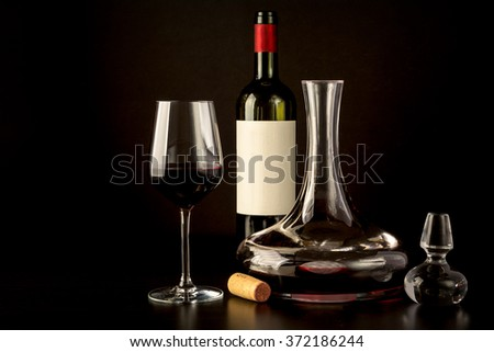 black background red wine glass, bottle decanter table reflections cork atmosphere  - stock photo