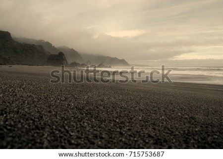Black beach with wild clouds