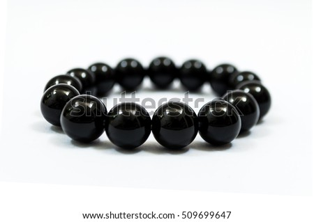 Black beads bracelet on white background. Simplified praying beads, use for counting prayers or practicing mindfulness meditation.