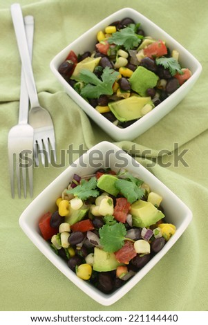 Black bean salad with avocado, corn, tomato, red onion and cilantro in vertical format