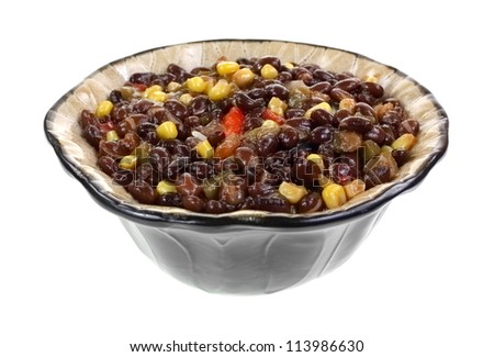 Black bean soup with slices of jalapeno pepper in a decorative bowl on a white background.