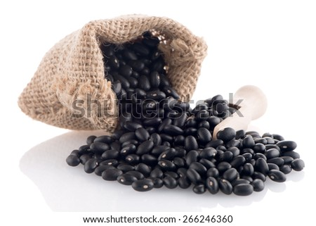 Black beans bag with wooden scoop on white background. - stock photo