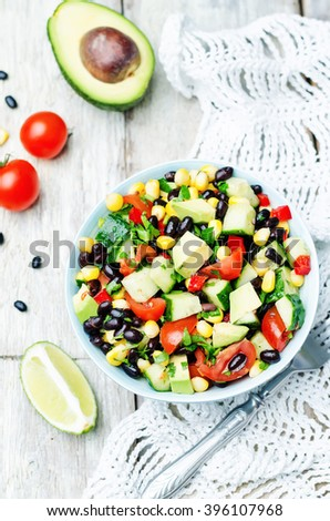 Black beans corn avocado cucumber tomato salad with lime dressing. toning. selective focus - stock photo